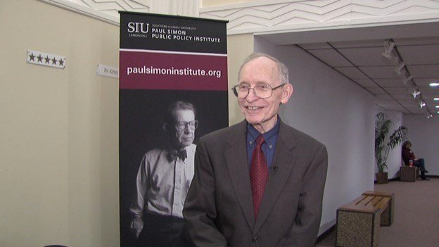Prof. John Jackson being interviewed by News 3 in front of a picture of the late Sen. Paul Simon.