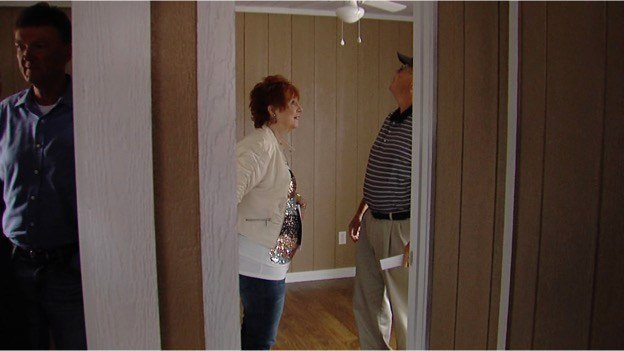 A man and woman look over one of the bedrooms