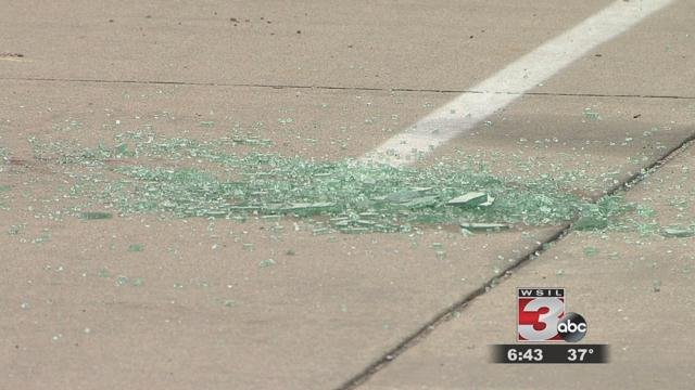 Shattered glass from a vehicle window pierced by bullets in the parking lot of an apartment complex in the 400 block of east Mill.