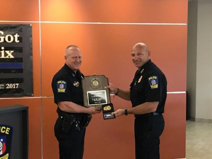 Decatur Police Chief Getz presents Officer Barrows with his retirement badge. Pic: Decatur Police Department